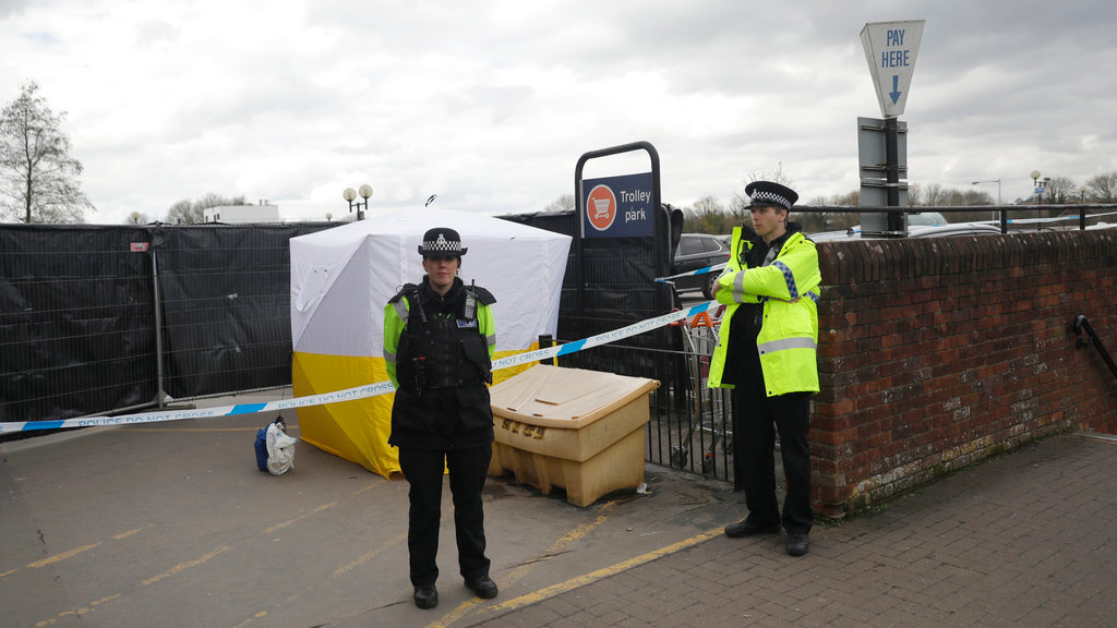 FILE - In this March 13, 2018, file photo, police officers guard a cordon around a police tent covering a supermarket car park pay machine near the spot where former Russian spy Sergei Skripal and his daughter were found critically ill following exposure to the Russian-developed nerve agent Novichok in Salisbury, England. The United States will impose sanctions on Russia for the country's use of a nerve agent in an assassination attempt on a former Russian spy and his daughter. (AP Photo/Matt Dunham, File)
