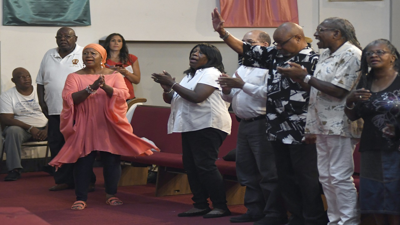 Church attendees sing during a prayer vigil for Aretha Franklin, Wednesday, Aug. 15, 2018 in Detroit. People are praying for Franklin in the Detroit church where her father was once a pastor.(Jose Juarez/Detroit News via AP)