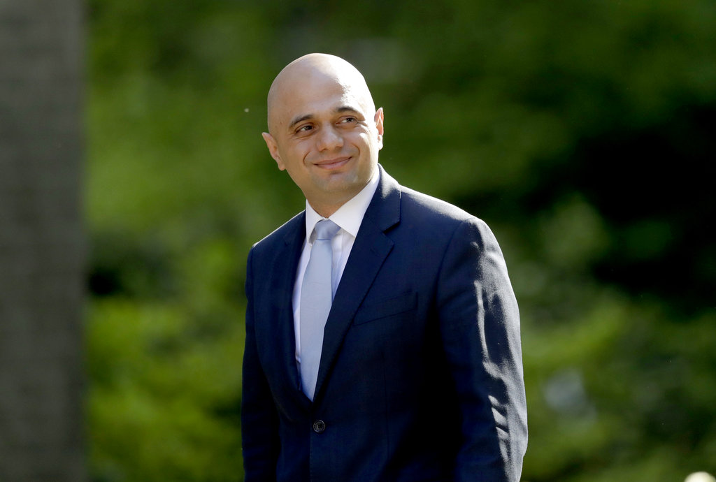 "Britain's newly appointed Home Secretary Sajid Javid. The British government has apologized to 18 long-term U.K. residents from the Caribbean who were deported or detained because they could not produce documents to prove their right to live in the country, with Home Secretary Javid saying their treatment was ""completely unacceptable,"" and has issued a personal apology, Tuesday Aug. 21, 2018. (AP Photo/Matt Dunham, FILE)"