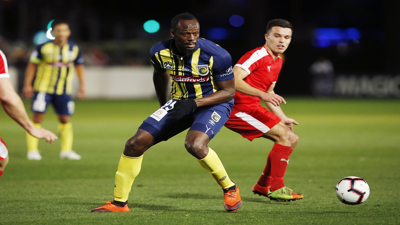 Usain Bolt runs the ball during a friendly trial match between the Central Coast Mariners and the Central Coast Select in Gosford, Australia, Friday, August 31, 2018. (AP Photo/Steve Christo)