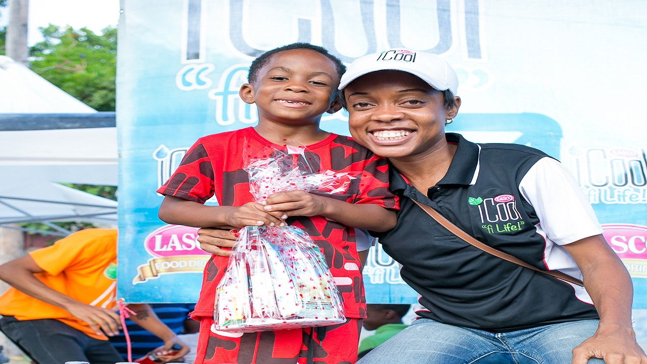 Five-year-old Jayquone Carby (left), who thrilled the crowd with his dance moves, happily collects his prize and shares a smile with Lyshon Davis (right), brand manager for LASCO iCool, at the iCool and Food Drink Community Link up at the Balmagie Football Field in Waterhouse.