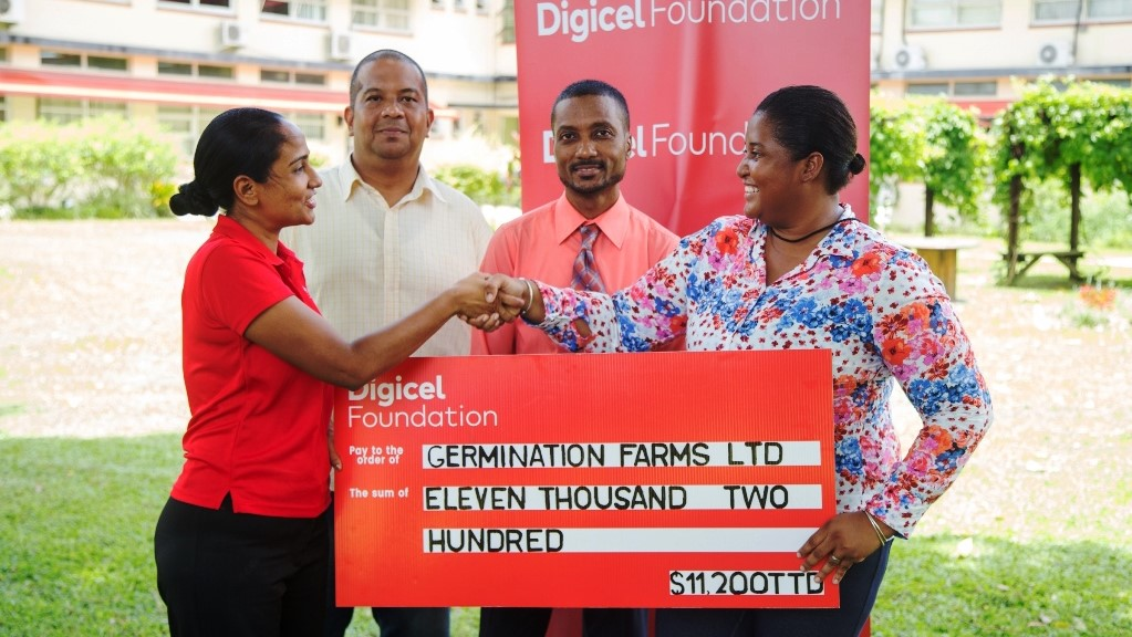 Diana Mathura-Hobson,Project Coordinator,Digicel Foundation (left) shakes hands with Kenia Campo, Managing Director of the Germi-Nation Farms Ltd. as she presents her with a cheque. Looking on are other members of the Germi-Nation Farms Ltd.