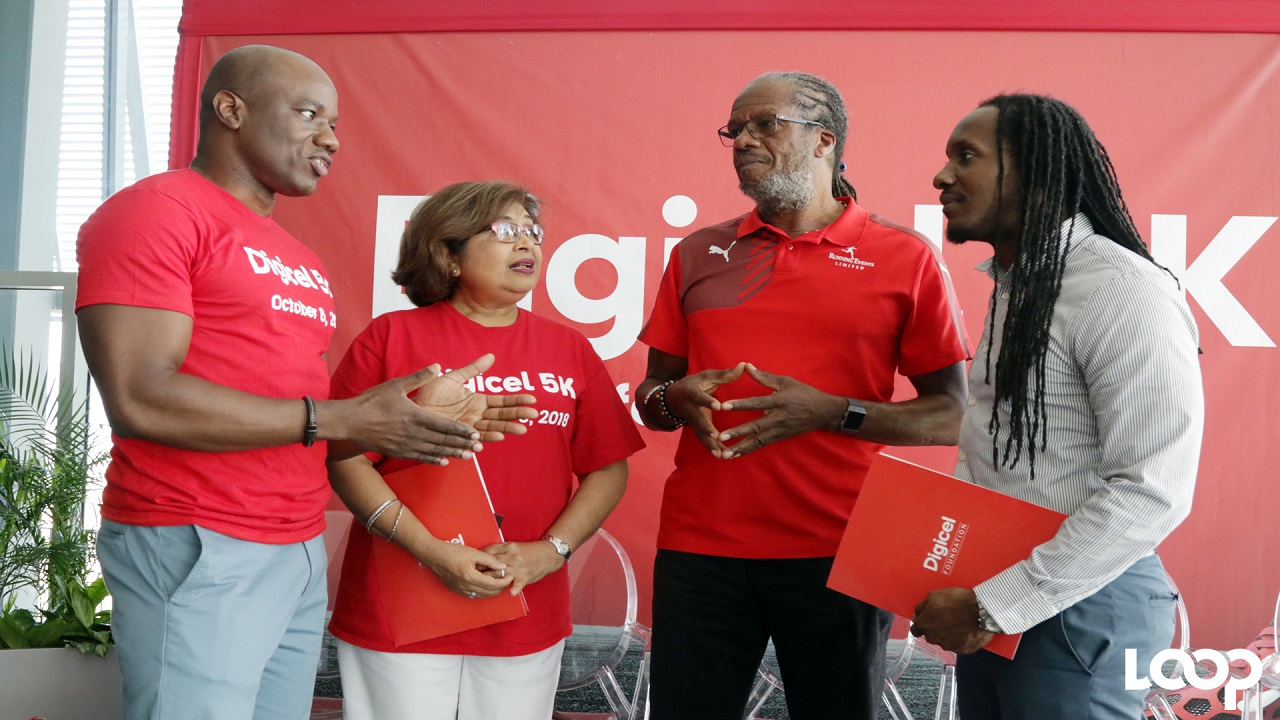 Elon Parkinson, Digicel's Regional Communications Manager (left) has the attention of (from left) Jean Lowrie-Chin, Chairman Digicel Jamaica Foundation; Alfred Francis, Managing Director Running Events Limited and Alando Terrelonge, state minister for Entertainment, Culture, Gender and Sport, at the launch of the seventh annual Digicel 5K Run/Walk for Special Needs at Digicel Headquarters in downtown Kingston on Friday. (PHOTO: Ramon Lindsay).