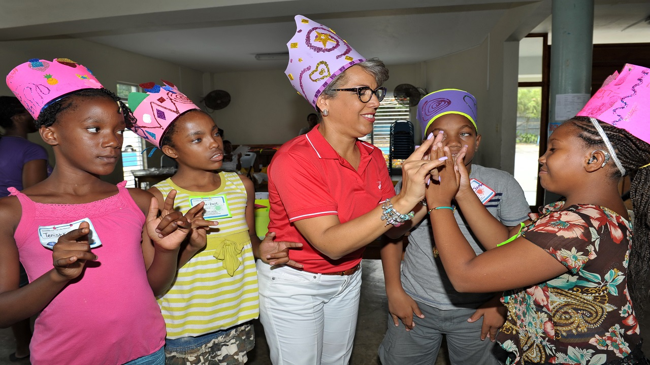 Lorri-Ann Lewis (right), one of the participants in the Jamaica Association of the Deaf (JAD) and Hope United Church summer programme gives a helping hand to Kim Mair (centre) as she gets an introduction to sign language, during one of the sessions in the summer programme. Also present are (L-R): Tenishka Morrison, Kanna-Kat Cover and Michael James.