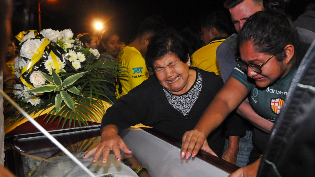 Relatives mourn over the coffin of a soccer fan killed in a bus crash at the Isidro Romero soccer stadium in Guayaquil, Ecuador, late Monday, Aug. 13, 2018. The bodies of 12 fans of Ecuadorean football team Barcelona that were killed when the bus they were traveling in after attending a local league match overturned were taken to the stadium for a collective funeral. (AP Photo/Jose Sanchez)