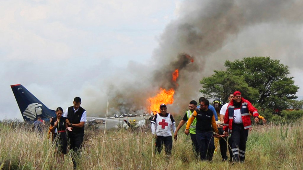 In this photo released by Red Cross Durango communications office, Red Cross workers and rescue workers carry an injured person on a stretcher, right, as airline workers, left, walk away from the site where an Aeromexico airliner crashed in a field near the airport in Durango, Mexico, Tuesday, July 31, 2018. The jetliner crashed while taking off during a severe storm, smacking down in a field nearly intact then catching fire, and officials said it appeared everyone on board escaped the flames.