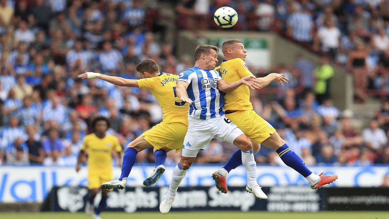 Huddersfield Town's Jonathan Hogg, centre, battles with Chelsea's Jorginho, left, and Ross Barkley during their English Premier League football match at the John Smith's Stadium in Huddersfield, England, Saturday Aug. 11, 2018.