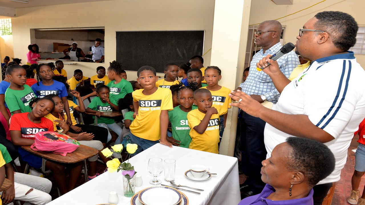 Parish Manager at the Greater St. Catherine SDC office, Samuel Heron (standing centre) addresses camp participants. Looking on are SDC field supervisor Lloyd Erskine (standing left) and retired teacher and 4-H Parish Advisory Committee Member Deloris Henry (seated right). Photo JIS.