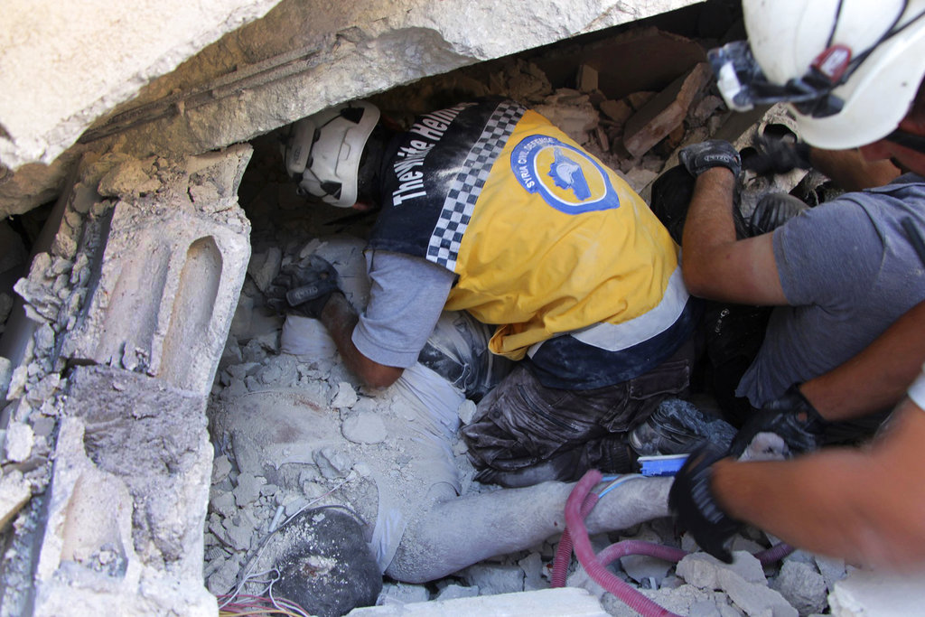This photo provided by the Syrian Civil Defense White Helmets, which has been authenticated based on its contents and other AP reporting, shows Syrian White Helmet civil defense workers remove a body from the rubble at the scene of an explosion that brought down a five-story building, in the village of Sarmada, near the Turkish border, north Syria, Sunday, Aug. 12, 2018. (Syrian Civil Defense White Helmets via AP)