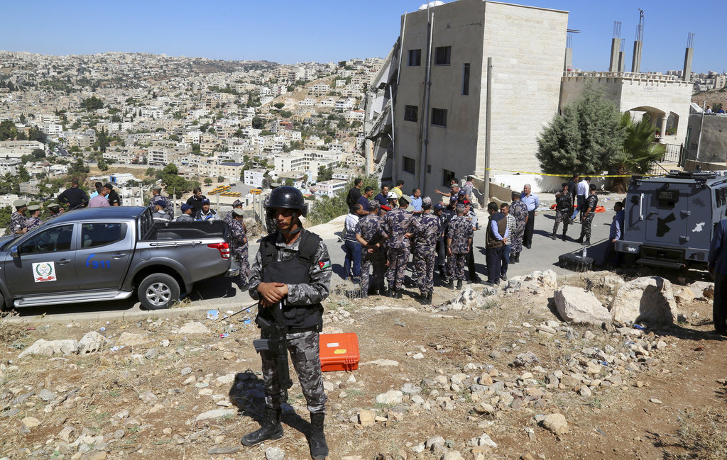 Jordanian forces secure the area Sunday, Aug. 12, 2018, after the side of a building collapsed when assailants opened fire and set off explosions late Saturday that killed four members of the security forces trying to storm the suspected militant hideout in Salt, west of the capital of Amman. Jordanian search teams have pulled the bodies of three suspected militants from the rubble of their hideout, a government official said Sunday. (AP Photo/Raad Adayleh)