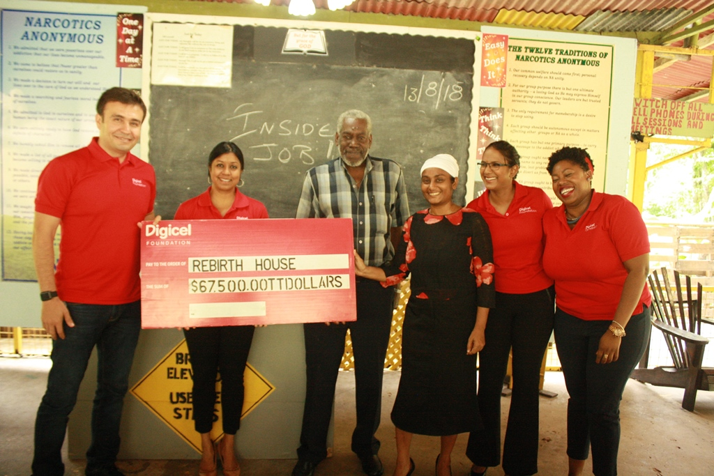 Jabbor Kayumov, Digicel's CEO (left) and Desha Clifford, Chairperson of the Digicel Foundation (2nd from left) presents a cheque to Steve Richards, Project Director and Dr. Valerie Ragbir, Rehabilitation Counsellor of Rebirth House. Also sharing in the moment are Nia Nanan, Project Officer (5th from left) and Cindyann Currency, Operations Manager of the Digicel Foundation