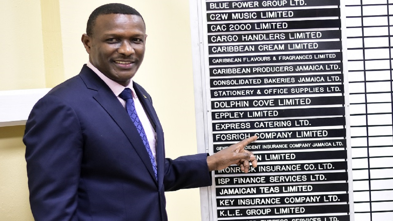 Fosrich Managing Director Cecil Foster points to his company's name on the trading board after listing.