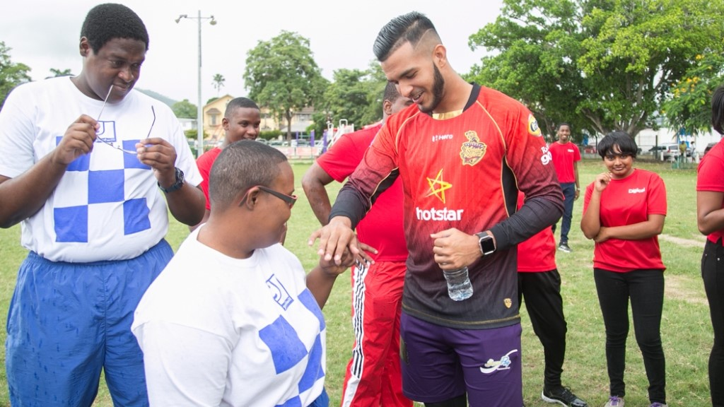 Amir Jangoo of the Trinbago Knight Riders (TKR) interacts with some of the students from the National Centre for Persons with Disabilities.