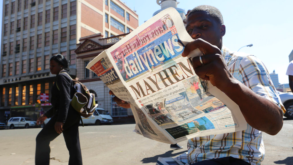 A man reads a newspaper headline in Harare, Zimbabwe,Wednesday, Aug, 2, 2018. (AP Photo/Tsvangirayi Mukwazhi)