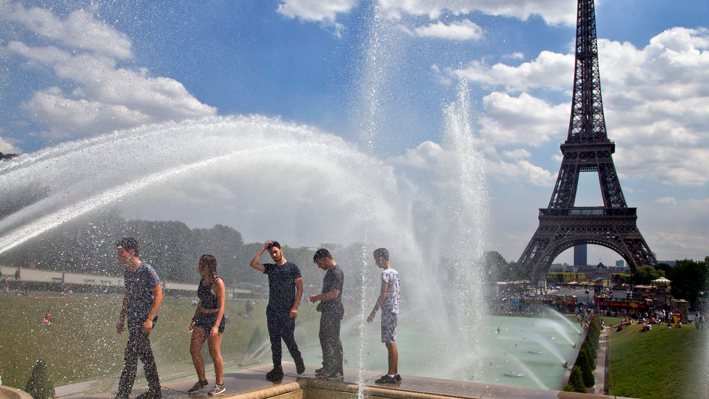 People cool off as they walk along the fountain of Warsaw near Eiffel Tower in Paris, France, Wednesday, Aug, 1, 2018. (AP Photo/Michel Euler)