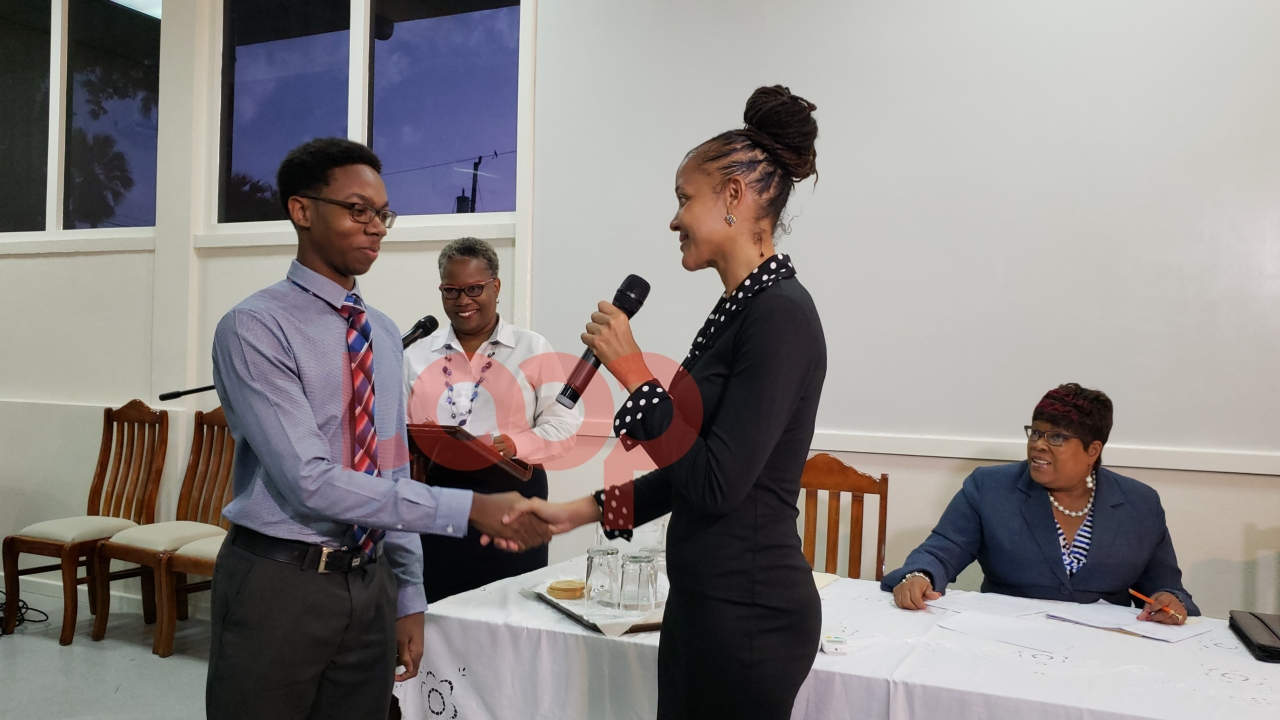 Nathan Lovell being thanked by the Minister of Education Technological and Vocational Training, Santia Bradshaw.