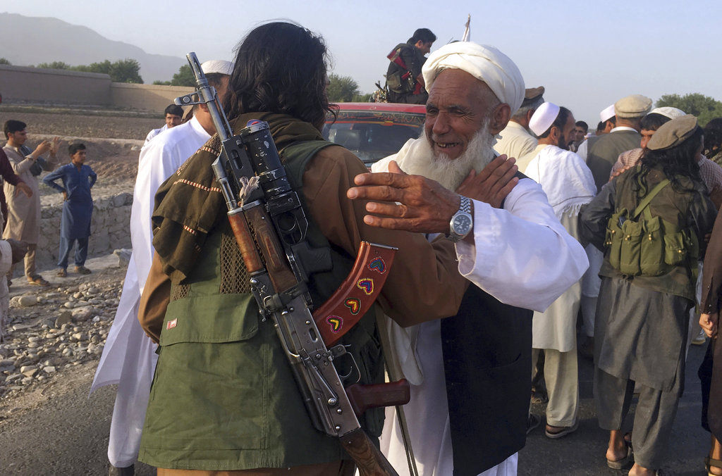 In this June 16, 2018 file photo, Taliban fighters gather with residents to celebrate a three-day cease fire marking the Islamic holiday of Eid al-Fitr, in Nangarhar province, east of Kabul, Afghanistan. On Sunday, Aug. 19, 2018, Afghan President Ashraf Ghani announced a conditional cease-fire with Taliban insurgents for the duration of the Eid al-Adha holiday. (AP Photo/Rahmat Gul, File)