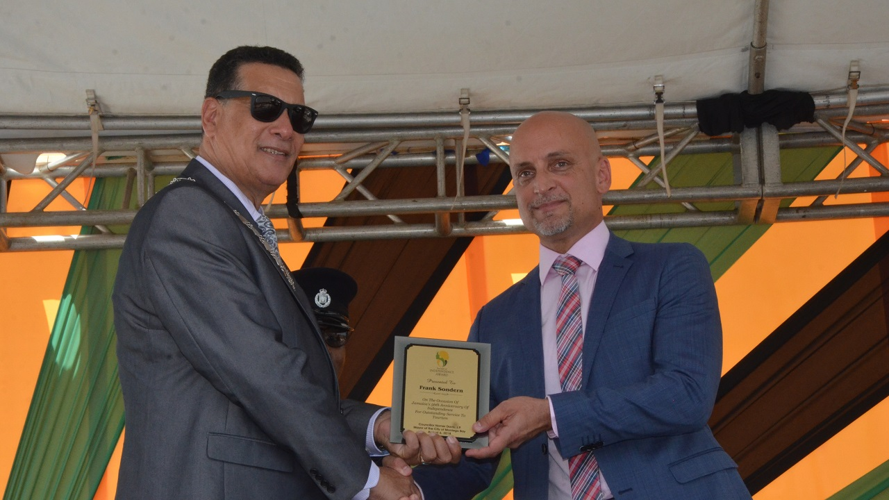 Senior general manager at RIU Reggae and RIU Jamaica Palace, Frank Sondern (right) accepts the Spirit of Independence award from Councillor Homer Davis, Mayor of Montego Bay.