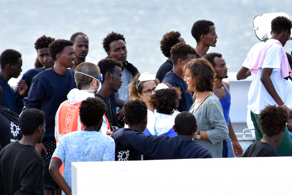 Migrants aboard the Italian Coast Guard ship Diciotti gather as they await decisions in the port of Catania, Italy, on Friday, August 24. (Orietta Scardino/ANSA via AP)