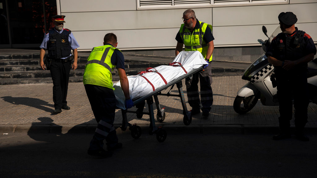 A body is taken on a stretcher by mortuary service members, outside a police station following an attack in Cornella de Llobregat near Barcelona, Spain, Monday, August 20, 2018. Police in Barcelona say they have shot a man who attacked officers with a knife at a police station in the Spanish city, saying in a tweet Monday the attack occurred just before 6 a.m. in the Cornella district of the city. (AP Photo/Emilio Morenatti)