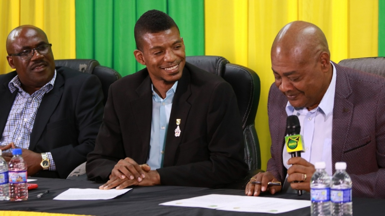 JFF President Michael Ricketts (right) makes a presentation during a press conference at the JFF headquarters on Thursday to announce an 18-man squad Under-23 squad to play two friendly games against St Vincent and the Grenadines. Also taking part in the presentation are Business Development Manager of the Jamaica Olympic Association Kirk Finnkin (centre) and JFF General Secretary Dalton Wint.