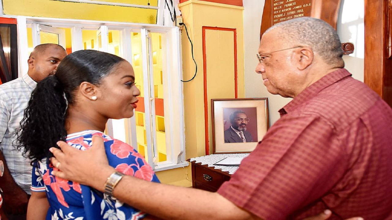 People's National Party president Dr Peter Phillips (right) offers his condolences to Councillor Kari Douglas over the passing of her father, former Cabinet minister Easton Douglas, while PNP General Secretary Julian Robinson looks on.