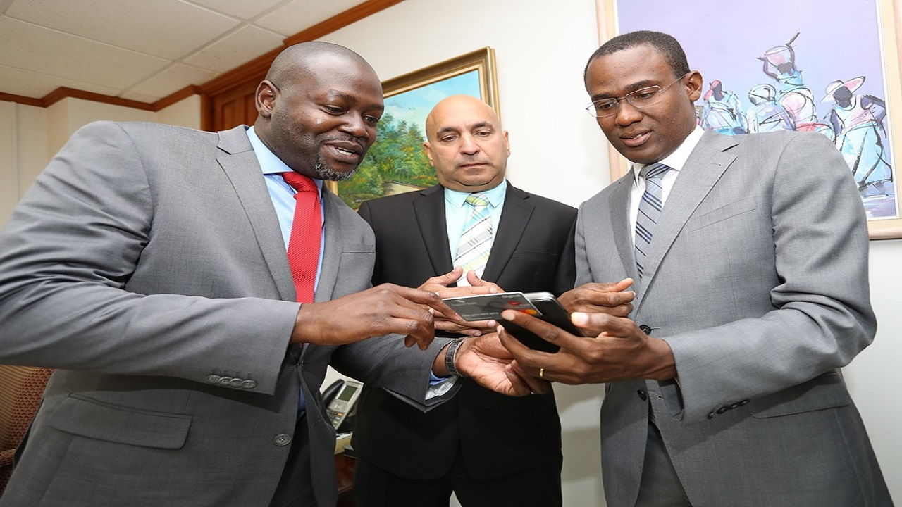 Fabian Williams, Digicel Group Chief Strategy Officer for MyCash (left), Sagicor Jamaica Group President and CEO Christopher Zacca (centre) examine the new MyCash card with Finance Minister Dr Nigel Clarke (right).