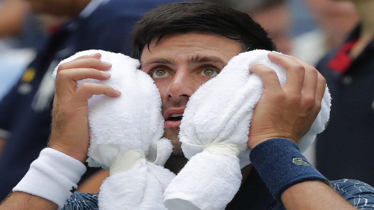Novak Djokovic, of Serbia, puts an ice towel to his face during a changeover in his match against Marton Fucsovics, of Hungary, during the first round of the U.S. Open tennis tournament, Tuesday, Aug. 28, 2018, in New York.