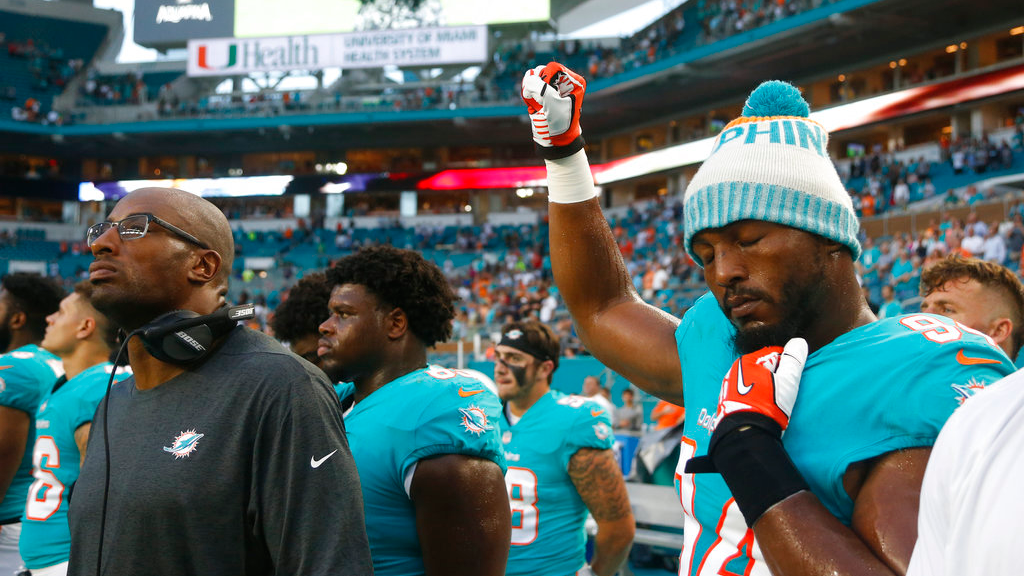 Photo: Miami Dolphins defensive end Robert Quinn (94) raises his right fist during the singing of the national anthem, before the team's NFL preseason football game against the Tampa Bay Buccaneers, Thursday, Aug. 9, 2018, in Miami Gardens, Fla. (AP Photo/Wilfredo Lee)
