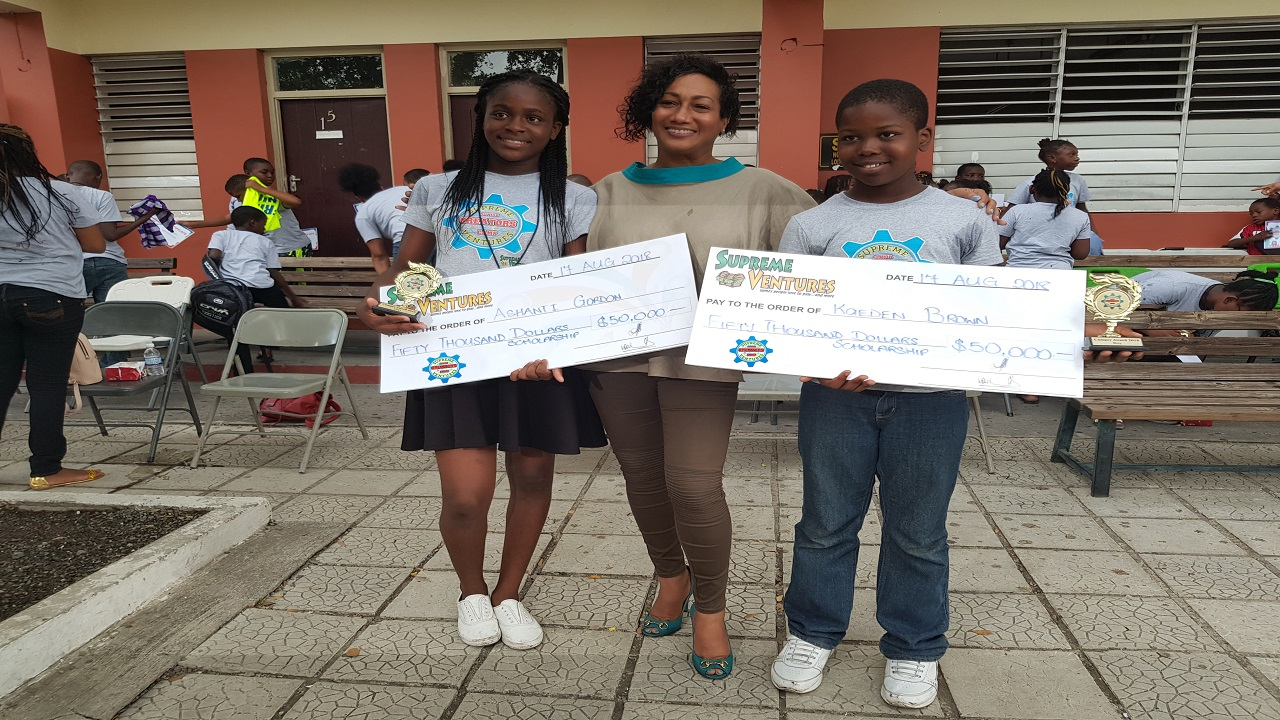 Top Boy and Girl, Kaeden Brown and Ashanti Gordon, receive their scholarship awards from Supreme Ventures Chief Marketing Officer, Heather Goldson during the prize giving ceremony.