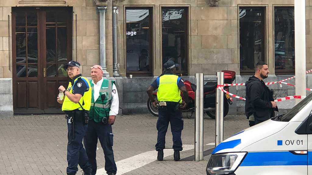 Dutch police officers near the scene of a stabbing attack near the central daily station in Amsterdam, the Netherlands, Friday Aug. 31, 2018. Police the Dutch capital shot and wounded a suspect Friday following a stabbing at the central railway station. Amsterdam police said in a series of tweets that two people were injured in the stabbing and the suspect was then shot by officers. (AP Photo/Alex Furtula)