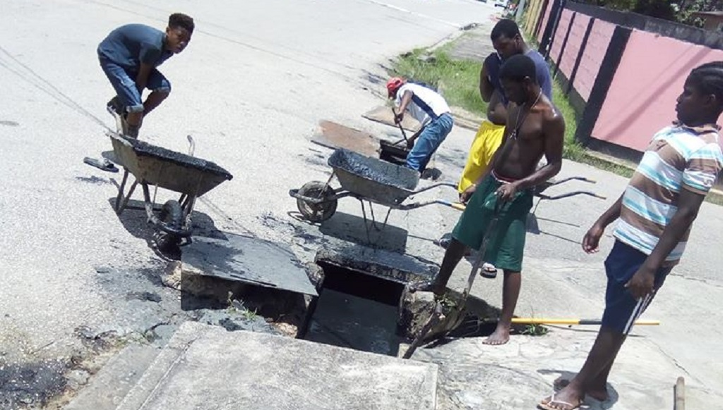 Photo: Youths from the Beetham community band together to clean drains after recent flooding. Without money for safety equipment many are at risk of injuries and ailments. They are asking for assistance before more flooding occurs. Photo courtesy Kareem Marcelle.
