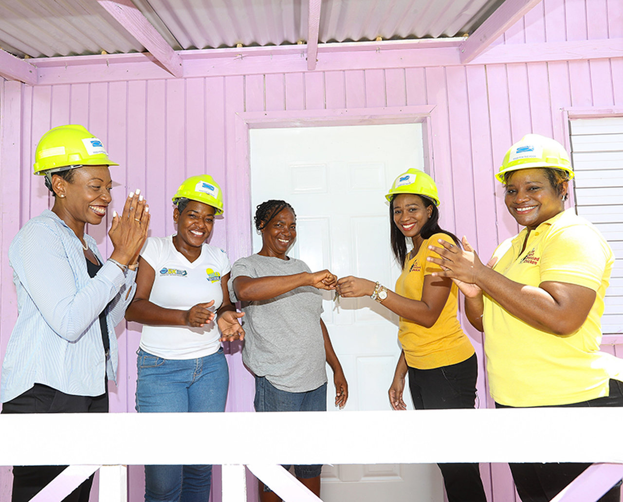 Rochelle Cameron, Assistant Vice President HRD & PR, Jamaica Broilers Group (left) applauds while Avadaugn Sinclair, BDC Marketing Manager (second right) hands Mrs. Howell (centre) the keys to her new home. Looking on are (left-right) Marsha Burrell-Rose, Development and Marketing Manager, Food for the Poor and Lorraine Kemble, BDC Brand Manager.