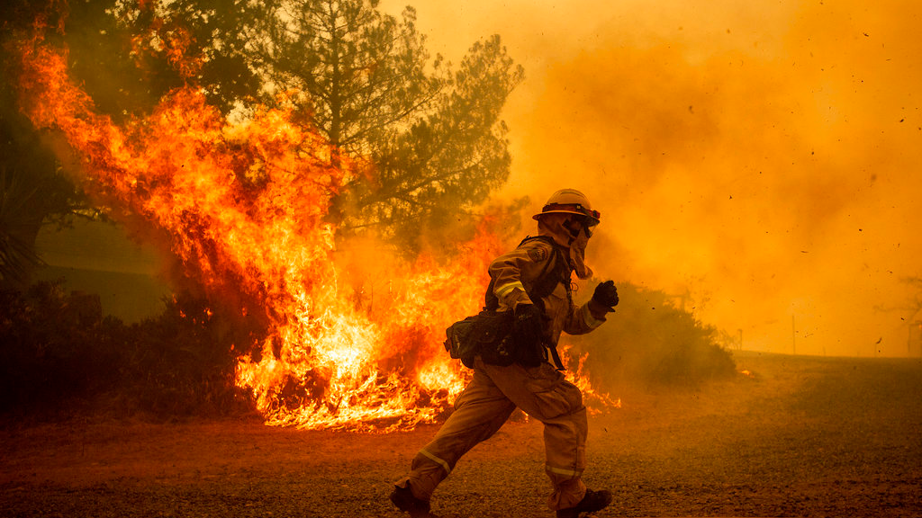 FILE - In this Tuesday, July 31, 2018, file photo, a firefighter runs while trying to save a home as a wildfire tears through Lakeport, Calif. The residence eventually burned. Authorities say a rapidly expanding Northern California wildfire burning over an area the size of Los Angeles has become the state's largest blaze in recorded history. (AP Photo/Noah Berger, File)