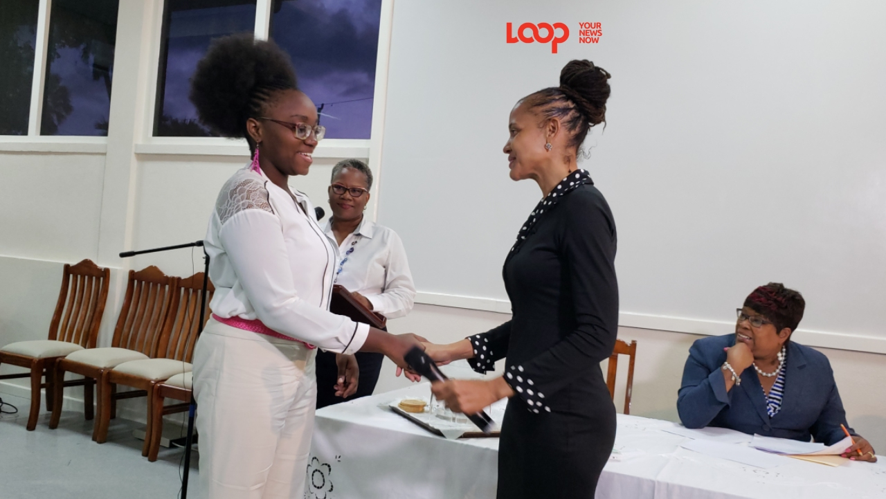 Barbados Communiy College Exhibition winner Naresa Mcrwray-Williams being congratulated by Minister Santia Bradshaw.