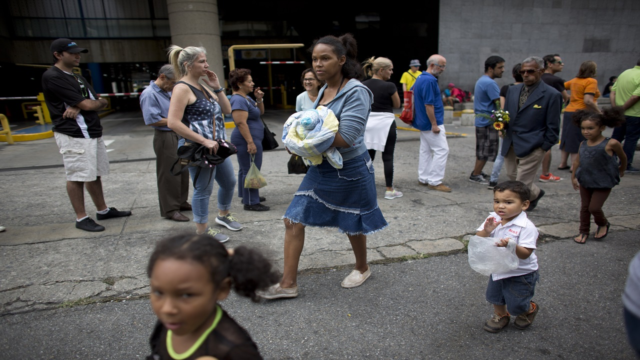 A woman holding a baby and walks with her children past people standing in line to buy food at a market in Caracas, Venezuela. (AP: Photo)
