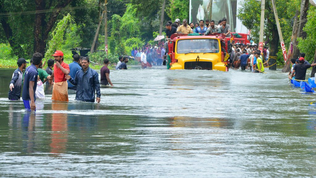 A truck carries people past a flooded road in Thrissur, in the southern Indian state of Kerala, Saturday, Aug. 18, 2018. Rescuers used helicopters and boats on Friday to evacuate thousands of people stranded on their rooftops following unprecedented flooding in the southern Indian state of Kerala that killed hundreds, officials said. (AP Photo)