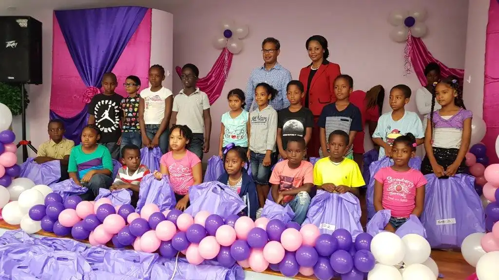 (Back row, L-R) Anil Seunath, Brand and Sponsorship Officer of Atlantic, and cricketer Merissa Aguilleira pause for a photo with children of the Marac community.
