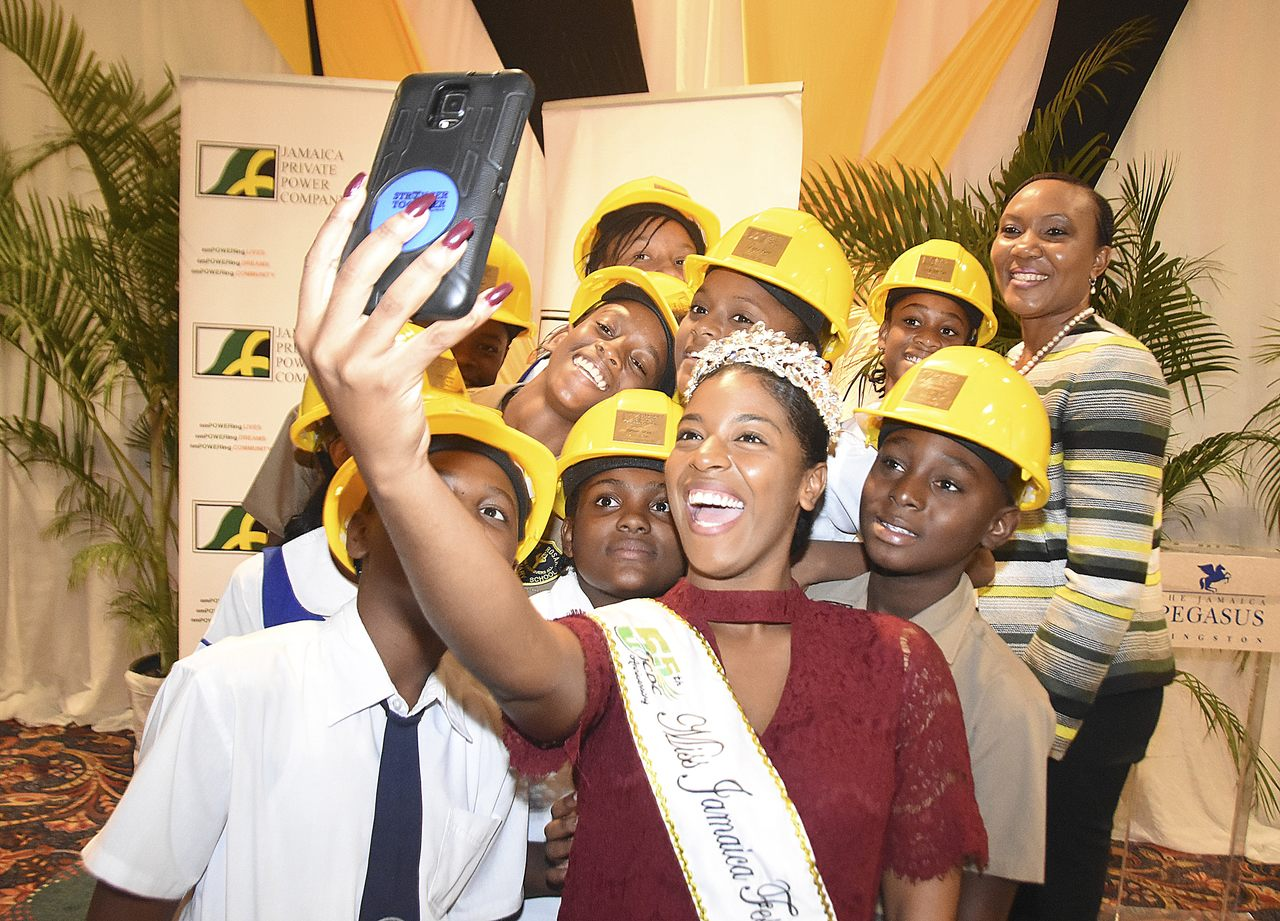 Ackera Gowie (right), Miss Jamaica Festival Queen uses her phone to take a selfie with the 2018 Jamaica Private Power Company (JPPC) G-SAT Scholarship recipients and the Power company's general manager, Ingrid Christian-Baker, after the ceremony held at the Jamaica Pegasus Hotel.