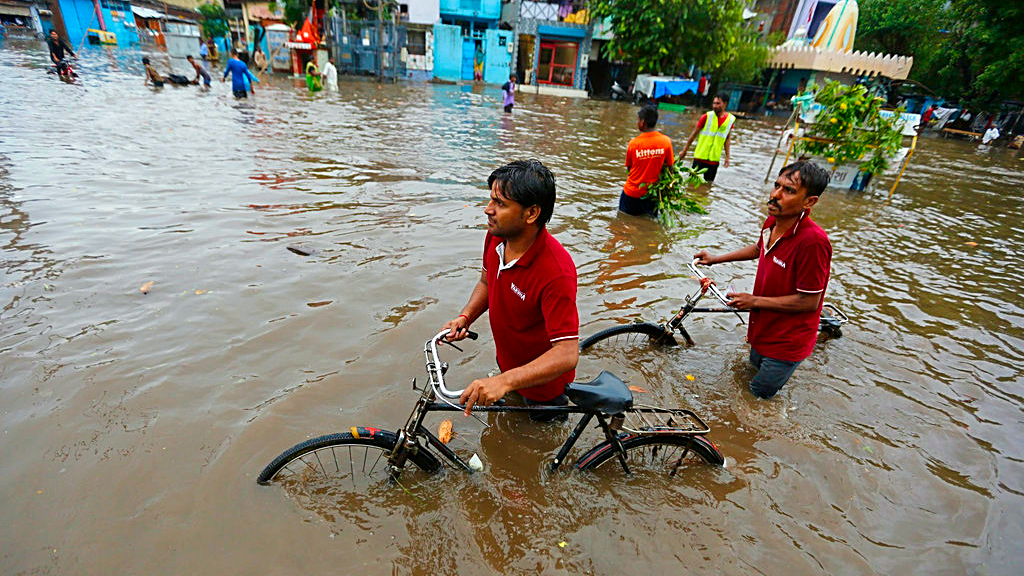 Indian men push their cycles past floodwaters after heavy rainfall in Ahmadabad, India, Friday, Aug. 17, 2018. India receives its annual rainfall from June-October. (AP Photo/Ajit Solanki)