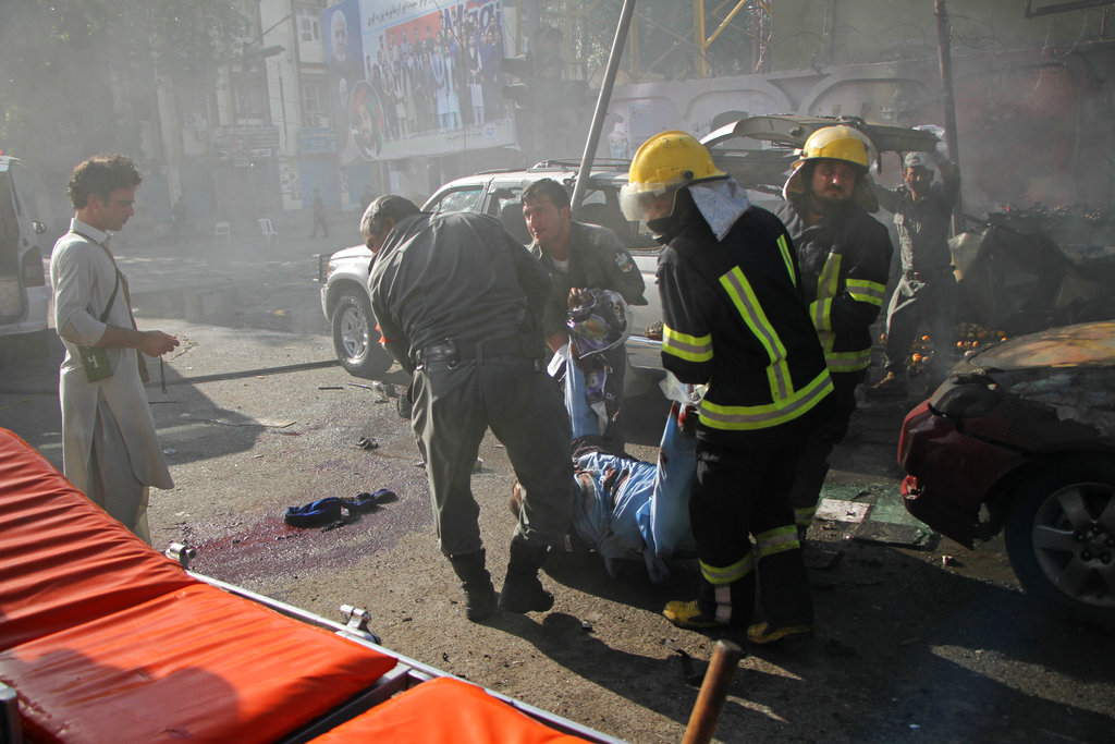 Police and firemen work at the site of a deadly suicide attack in Jalalabad, Afghanistan Thursday, June 7, 2018. A suicide bomber targeted a group of Sikhs and Hindus on their way to meet Afghanistan's president in the eastern city of Jalalabad on Sunday, killing at least 19 people including Avtar Singh Khalsa, a longtime leader of the Sikh community who had planned to run in the parliamentary elections set for October. (AP Photo)