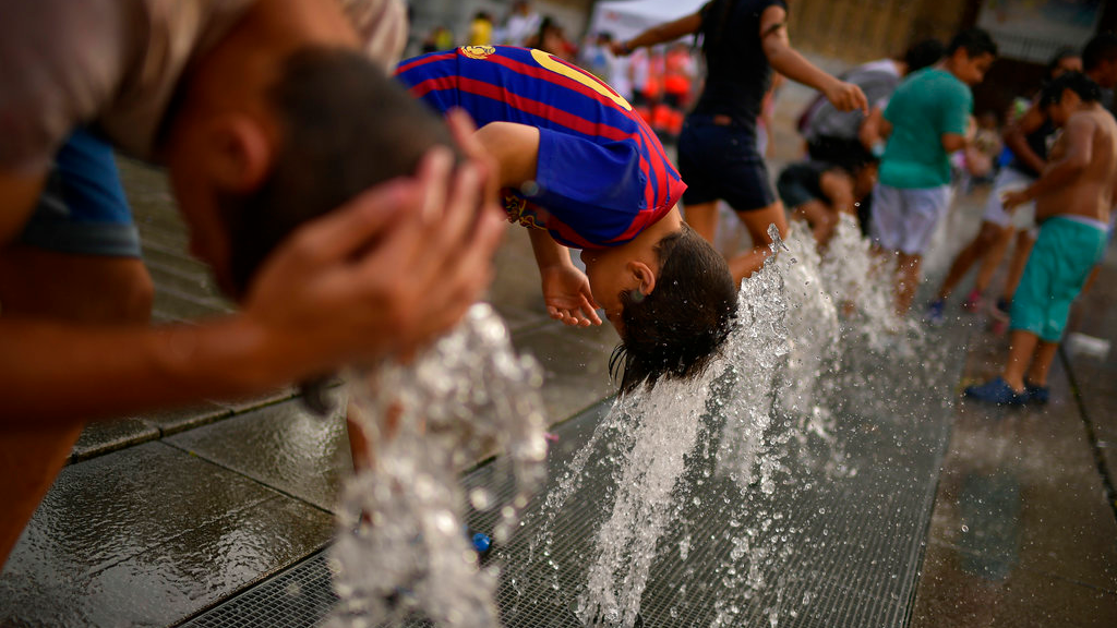 People cool off with water from a fountain during a hot summer day, in the basque city of Vitoria, northern Spain, Saturday, Aug. 4, 2018. Hot air from Africa is bringing a heat wave to Europe, prompting health warnings about Sahara Desert dust and exceptionally high temperatures that could peak at 47 degrees Celsius (117 Fahrenheit) in Spain and Portugal. (AP Photo/Alvaro Barrientos)