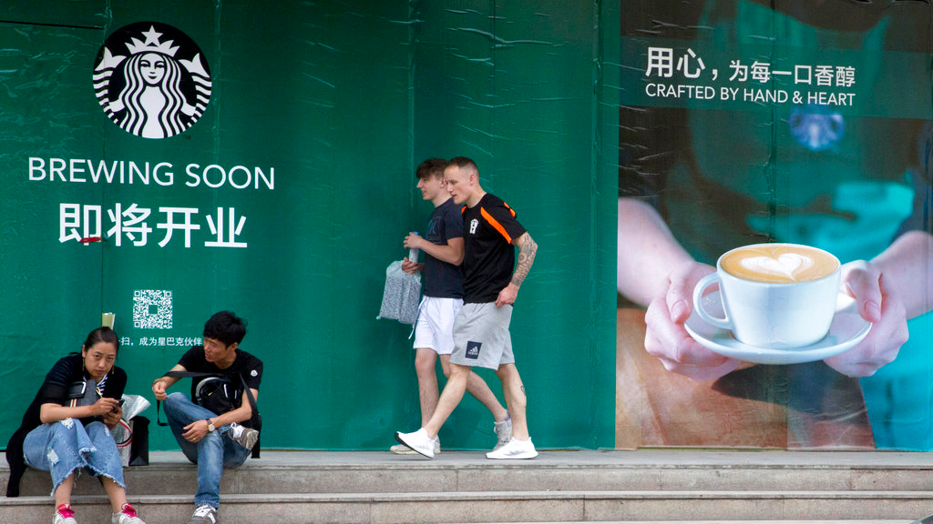 In this photo taken Wednesday, May 16, 2018, foreigners walk past a man and woman outside a Starbucks outlet under construction in Beijing, China. (AP Photo/Ng Han Guan)