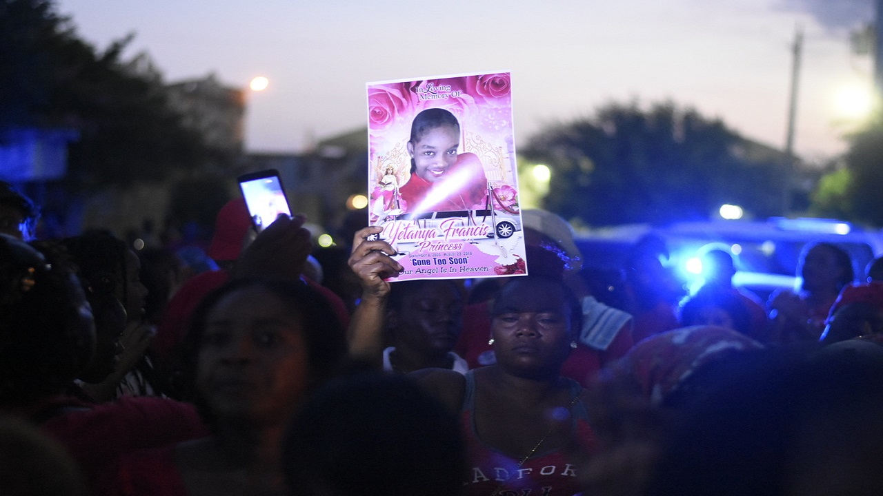 A mourner displays a photo of the late Yetanya Francis at a candlelight vigil held in her honour on Wednesday evening in Arnett Gardens. (PHOTO: Marlon Reid)