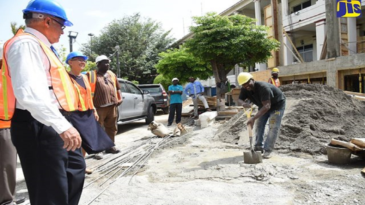 Justice Minister, Delroy Chuck (left), and Head of Delegation of the European Union (EU) to Jamaica, Ambassador Malgorzata Wasilewska (second left), observe as a workman mixes cement during a tour of the Court of Appeal building on King Street, downtown Kingston, which is being expanded to house more courtrooms and other facilities. The tour was conducted on August 9.