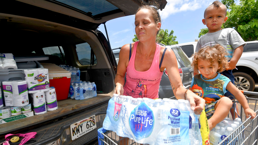Brianna Sugimura unloads supplies for riding out the storm while her children, Radon-Kai and Kanaloa watch in the parking lot of a Walmart store Tuesday, Aug. 21, 2018, in Lihue, on the island of Kauai in Hawaii. (Dennis Fujimoto/The Garden Island via AP)