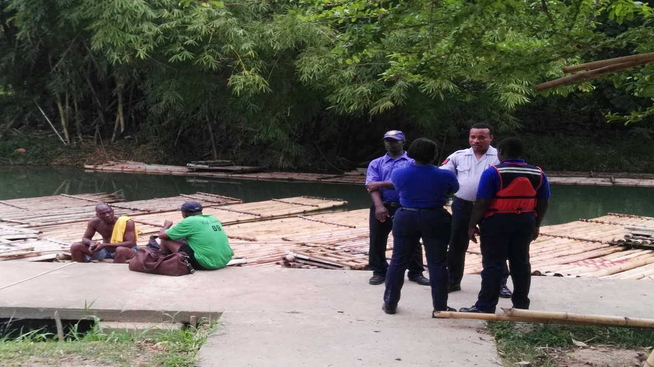 A group of public officers, including divers, are pictured at a point along the Martha Brae River in Trelawny where search efforts were under way on Tuesday for two persons who are believed to have drowned in the waters.
