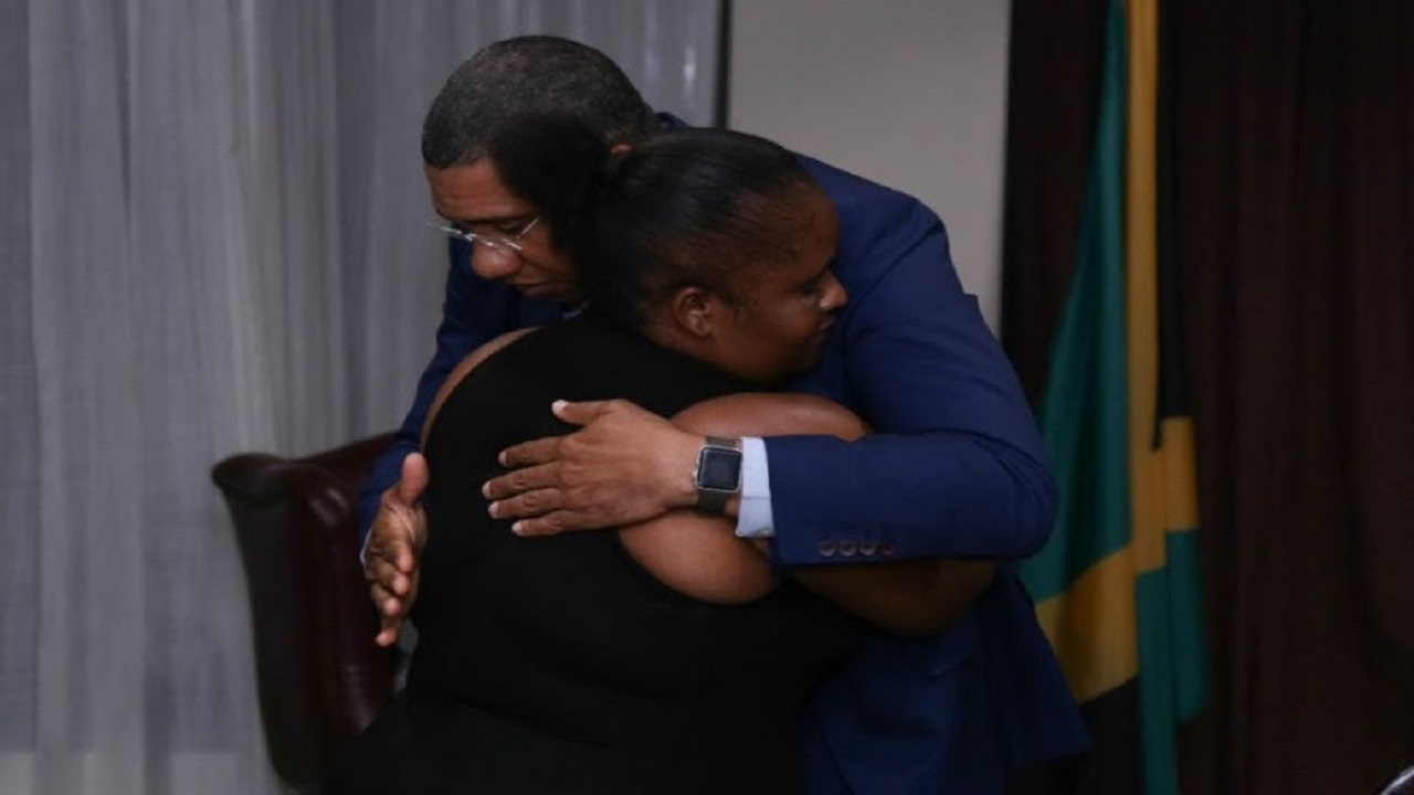 Prime Minister Andrew Holness consoles Latoya Riley, mother of 14-year-old Yetanya Francis, who was murdered last week.