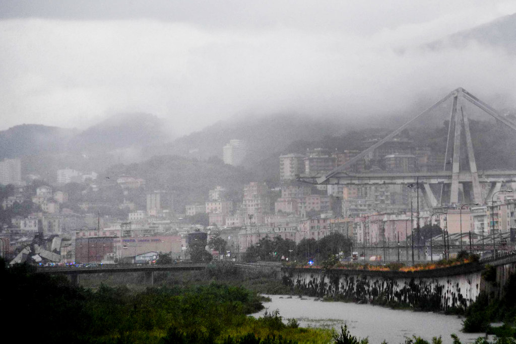 view of the collapsed Morandi highway bridge in Genoa, Tuesday, Aug. 14, 2018. Italian authorities say that about 10 vehicles were involved when the raised highway collapsed during a sudden and violent storm in the northern port city of Genoa, while private broadcaster Sky TG24 said the collapsed section was about 200-meter long (650 feet). (Luca Zennaro/ANSA via AP)