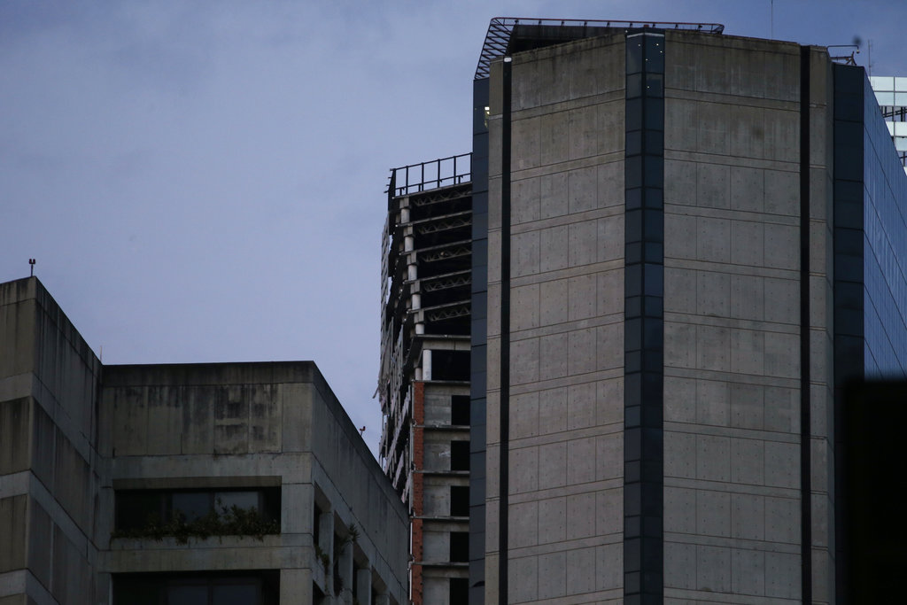 "An abandoned, unfinished skyscraper known as ""The Tower of David"" shows an inclination on the top floors where the columns are exposed, top center, after a powerful earthquake shook eastern Venezuela, causing buildings to be evacuated in the capital of Caracas, Venezuela, Tuesday, Aug. 21, 2018. (AP Photo/Ariana Cubillos)"